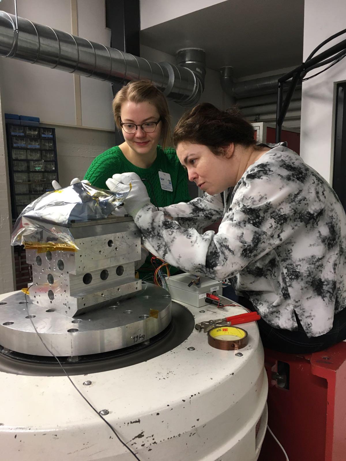 Mariat Genzer ja Hieta valmistelemassa avaruuslaitetta tärinätestiin.